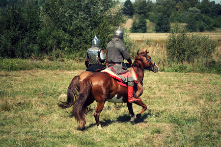 Reconstruction. Two medieval armored knights on horses from fantasy. Equestrian soldiers in historical costumes is in the summer field
