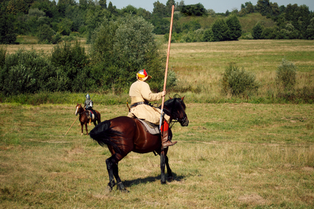 Knight tournament. Medieval armored riders with lances on horses. Equestrian soldiers are in the summer field