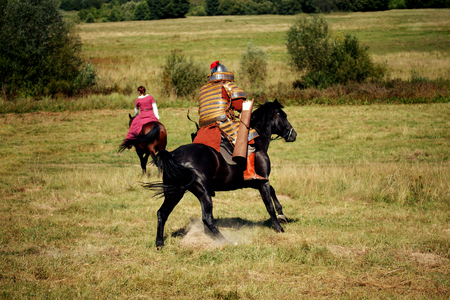 War and mercenary on a horse. Medieval equestrian robber chases the horseback woman