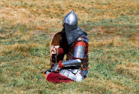 Medieval warrior in armor. Soldier in historical costume is in the summer field