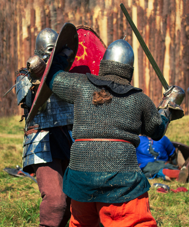 Cosplay. Two medieval warriors in armor are fighting Stock Photo