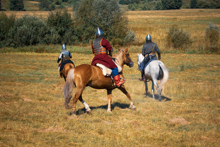 Three medieval armored knights on horses. Equestrian soldiers in historical costumes is in the summer field Stock Photo