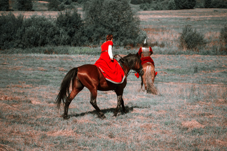 Reconstruction. Medieval horsewoman and horseman are riding their horses in the steppe