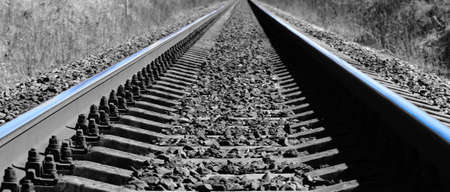 Empty railroad track going into the distance, out brightly in gray landscape. Perspective view Standard-Bild - 155341883