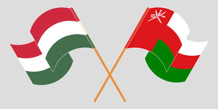 Crossed and waving flags of Oman and Hungary