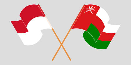 Crossed and waving flags of Oman and Indonesia