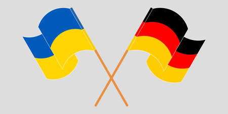 Crossed and waving flags of the Ukraine and Germany