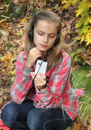 girl listening to music in the headset with a mobile phone photo