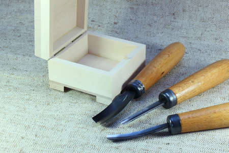 wood cutter: three of the cutter for wood and wooden box on the canvas Stock Photo