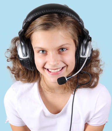 a pretty curls smiling girl in the headphones with a microphone  isolated on blue photo