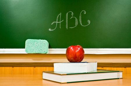 juicy apple and book at school on a background a board