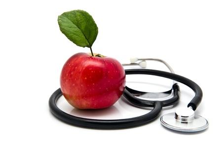 estetoscopio corazon: manzana y stetoskop sobre un fondo blanco Foto de archivo
