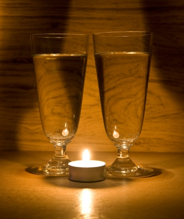 candle and glasses on a wooden table photo