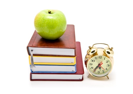 books, clock and apple on a white background photo
