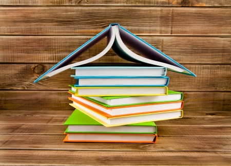 pile of books on a wooden background photo