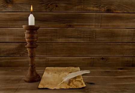 feather, old paper and candle on a wooden background 版權商用圖片