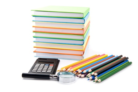 books, calculator, pencils and magnifying glass on a white background photo