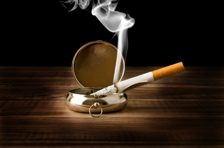 ash-tray with a cigarette on a black background photo
