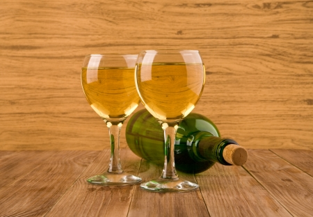 two glasses of wine and bottle on a wooden table photo