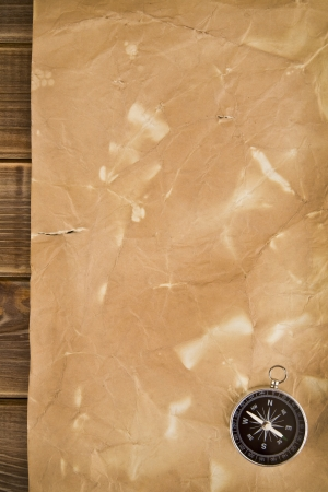 old paper and compass on a wooden background photo