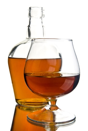 bottle and glass with cognac on a white background