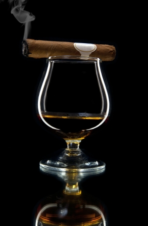 alcohol and smoking a cigar on a black background Stock Photo