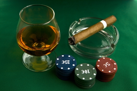 alcohol, chips and cigar on a green background photo