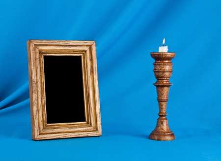 wooden photo frame and candle on a blue background photo