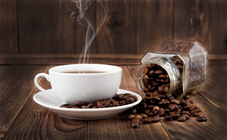 cup and grains of coffee on a wooden background photo