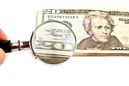 dinero falso: dólares y lupa sobre un fondo blanco Foto de archivo