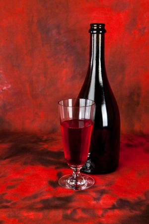 glass and bottle of wine on a red background photo