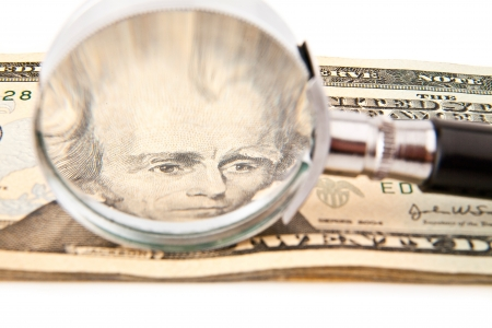 dollars and magnifying glass on a white background photo