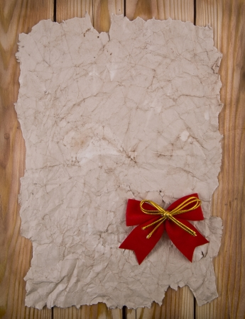 old paper with a bow on a wooden background photo