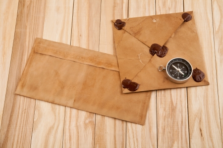 old envelopes and compass on a table
