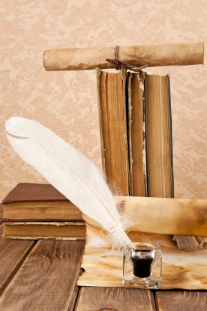 inkstand: old books and pen on a wooden table Stock Photo