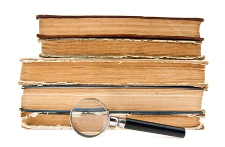 old books and magnifying glass on a white background photo