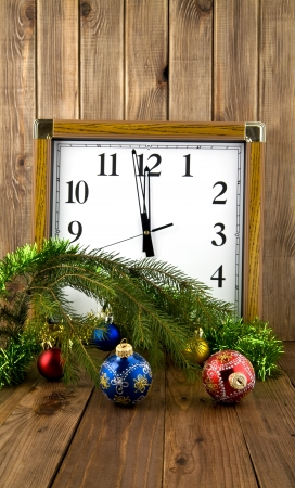christmas decorations and the clock on the wooden background  photo
