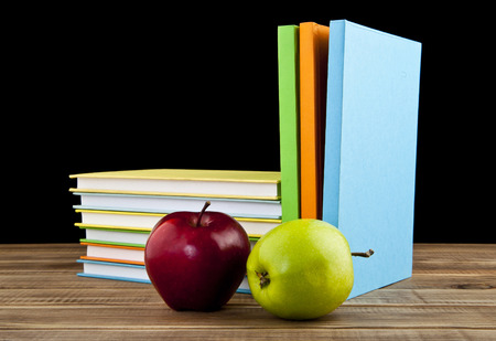apples and books on a black background photo