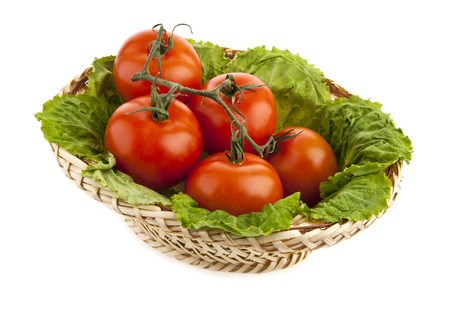 fresh tomatoes in a basket on a white background photo