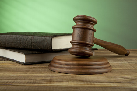 court judge: wooden mallet and books on a green background