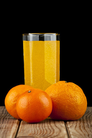 oranges and juice on a black background photo