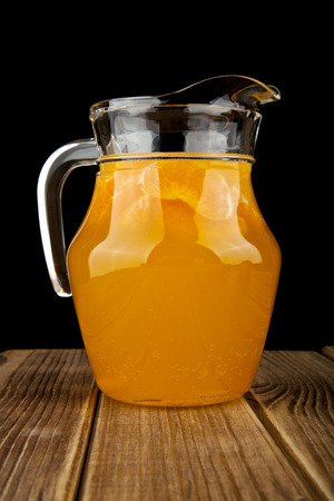 jug with orange juice on a black background photo