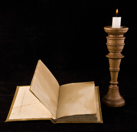 old books with a candle on a black background photo