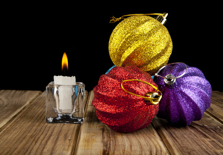 candle and Christmas ornament on a black background photo