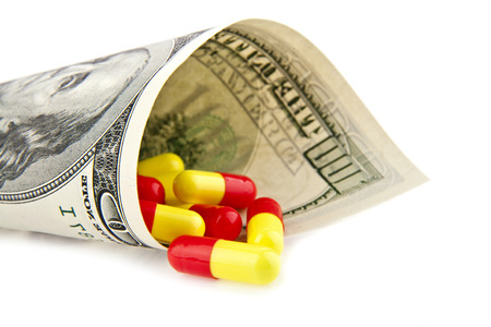 health care funding: pills and dollars on a white background.