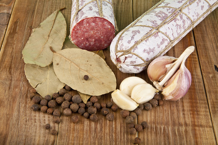 salame: salame, garlic and laurel leaves on a wooden table