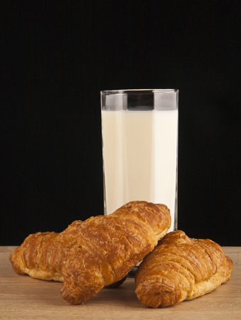 elevenses: milk and croissants on a black background