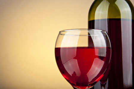 white wine glass: glass of wine and a bottle on a yellow background