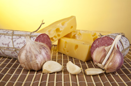 salame: salame, garlic and laurel leaves on a yellow background Stock Photo