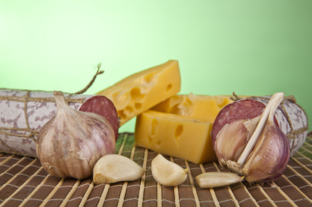 longaniza: salame, garlic and laurel leaves on a green background Stock Photo